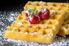 Sweet toast waffles with raspberries and a sprig of mint leaves and sugar powder close-up macro on black background. Sweet toast waffles with raspberries and a Royalty Free Stock Images