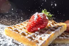 Sweet toast waffles with strawberry with leaves on top and sifting pouring sugar powder in the sunlight close-up Stock Image
