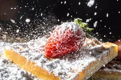 Sweet toast waffles with strawberry with leaves on top and sifting pouring sugar powder in the sunlight close-up Royalty Free Stock Photo