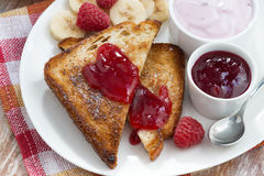 Sweet toasts with fresh raspberry, jam and yoghurt for breakfast Stock Photography