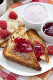 Sweet toasts with fresh raspberry, jam and yoghurt for breakfast Stock Photo