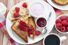 Sweet toasts with fresh raspberry, jam and yoghurt for breakfast. Top view, horizontal Royalty Free Stock Photography