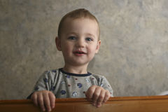 Sweet Toddler. Two year old male toddler looking at camera.  The toddler is smiling from his crib.  Shot at a low angle Royalty Free Stock Image