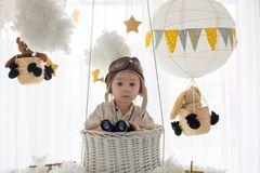 Sweet toddler boy, playing with airplane and teddy bear, air balloons with toys behind him