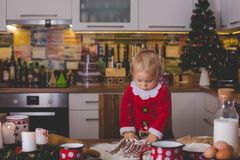 Sweet toddler child, boy, helping mommy preparing Christmas cook royalty free stock photography