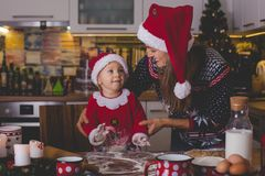 Sweet toddler child, boy, helping mommy preparing Christmas cook stock images