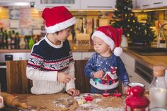 Sweet toddler child and his older brother, boys, helping mommy p. Reparing Christmas cookies at home in kitchen royalty free stock photos