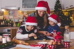 Sweet toddler child and his older brother, boys, helping mommy p. Reparing Christmas cookies at home in kitchen stock photography