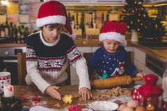 Sweet toddler child and his older brother, boys, helping mommy p. Reparing Christmas cookies at home in kitchen royalty free stock images