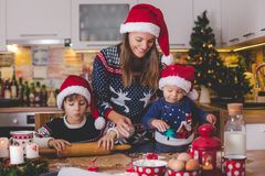 Sweet toddler child and his older brother, boys, helping mommy p. Reparing Christmas cookies at home in kitchen stock photos