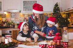 Sweet toddler child and his older brother, boys, helping mommy p. Reparing Christmas cookies at home in kitchen stock image