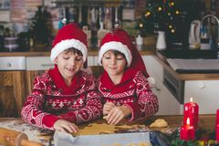 Sweet toddler child and his older brother, boys, helping mommy p. Reparing Christmas cookies at home in kitchen stock images