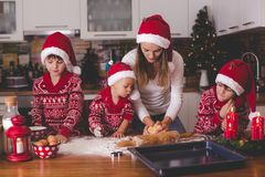 Sweet toddler child and his older brother, boys, helping mommy preparing Christmas cookies at home. In kitchen royalty free stock photography