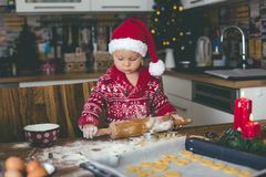 Sweet toddler child and his older brother, boys, helping mommy preparing Christmas cookies at home. In kitchen stock photo