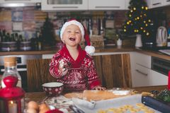 Sweet toddler child and his older brother, boys, helping mommy preparing Christmas cookies at home stock photos