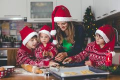 Sweet toddler child and his older brother, boys, helping mommy p. Reparing Christmas cookies at home in kitchen royalty free stock photo