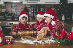 Sweet toddler child and his older brother, boys, helping mommy preparing Christmas cookies at home. In kitchen royalty free stock photo