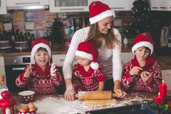 Sweet toddler child and his older brother, boys, helping mommy preparing Christmas cookies at home royalty free stock photography