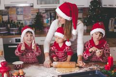 Sweet toddler child and his older brother, boys, helping mommy preparing Christmas cookies at home. In kitchen royalty free stock photos