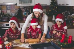 Sweet toddler child and his older brother, boys, helping mommy preparing Christmas cookies at home. In kitchen stock image