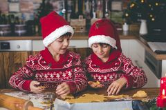 Sweet toddler child and his older brother, boys, helping mommy preparing Christmas cookies at home royalty free stock image