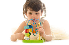 Sweet toddler girl concentrated playing with educational baby wo Stock Photo