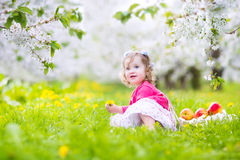 Sweet toddler girl eating apple in blooming garden Stock Photography