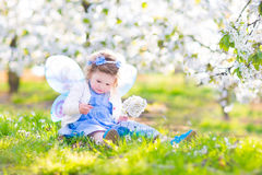 Sweet toddler girl in fairy costume in fruit apple garden. Adorable toddler girl with curly hair and flower crown wearing a magic fairy costume with a blue dress Stock Photo