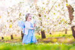 Sweet toddler girl in fairy costume in fruit garden. Adorable toddler girl with curly hair and flower crown wearing a magic fairy costume with a blue dress and Stock Photo