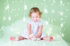 Sweet toddler girl with her bear toy sitting between green Christmas lights Stock Images