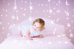 Sweet toddler girl playing on a bed between warm soft Christmas l Stock Image