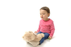 Sweet toddler girl playing with her teddy bear putting him on feet to sleep. Isolated stock photography