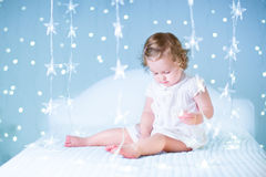 Sweet toddler girl playing with her toy bear between soft lights in star shape Royalty Free Stock Images