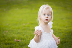 Sweet Toddler Girl Wearing White Dress In A Grass Field Stock Photo