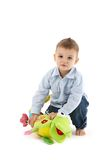 Sweet toddler with soft toy. Sweet toddler boy playing with colorful soft toy, smiling, looking at camera stock photos