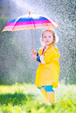Sweet toddler with umbrella playing in the rain Stock Photography