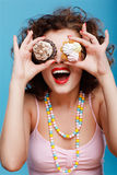 Sweet tooth. Portrait of beautiful curly brunette girl with two tarts Royalty Free Stock Image