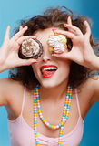 Sweet tooth. Portrait of beautiful curly brunette girl with two tarts Royalty Free Stock Photos