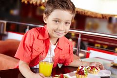 Sweet-tooth. Portrait of a cute boy with three portions of dessert at the cafe Royalty Free Stock Photo