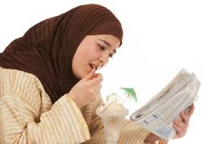 Sweet tooth. Young islamic woman reading her newspaper while enjoying an ice cream Stock Images
