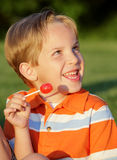 Sweet Tooth. Happy little blond boy eating a candy lollipop at a park and smiling big Royalty Free Stock Images