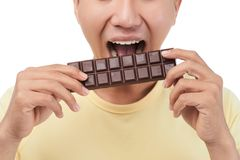 Sweet Tooth Biting Chocolate Bar. Close-up shot of unrecognizable man wearing yellow T-shirt biting chocolate bar while standing against white background stock photo