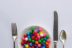 Sweet tooth. Bright gumballs as main dish at a styled table setting. Copy space Stock Photo