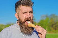 Sweet tooth concept. Bearded man with ice cream cone. Man with long beard licks ice cream. Man with beard and mustache. On strict face eats ice cream, blue sky royalty free stock images