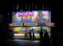 Sweet Tooth Delight!. A cotton candy and sweets stand at a local carnival.  silhouettes contrasting against the colorful lights make the image pop! A local fair Stock Photos