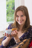Sweet tooth girl eating eclairs. Portrait of sweet tooth girl enjoying eclairs and coffee Stock Photography
