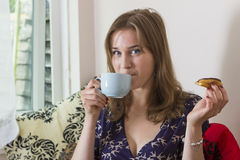 Sweet tooth girl eating eclairs. Portrait of sweet tooth girl enjoying eclairs and coffee Royalty Free Stock Photography