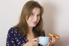 Sweet tooth girl eating eclairs. Portrait of sweet tooth girl enjoying eclairs and coffee Stock Images