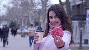 Sweet tooth, hungry girl with pastry and warming drinks in plastic cup outdoors in city. Close-up stock video