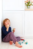 Sweet tooth kid hiding in kitchen corner, eating candies Royalty Free Stock Images